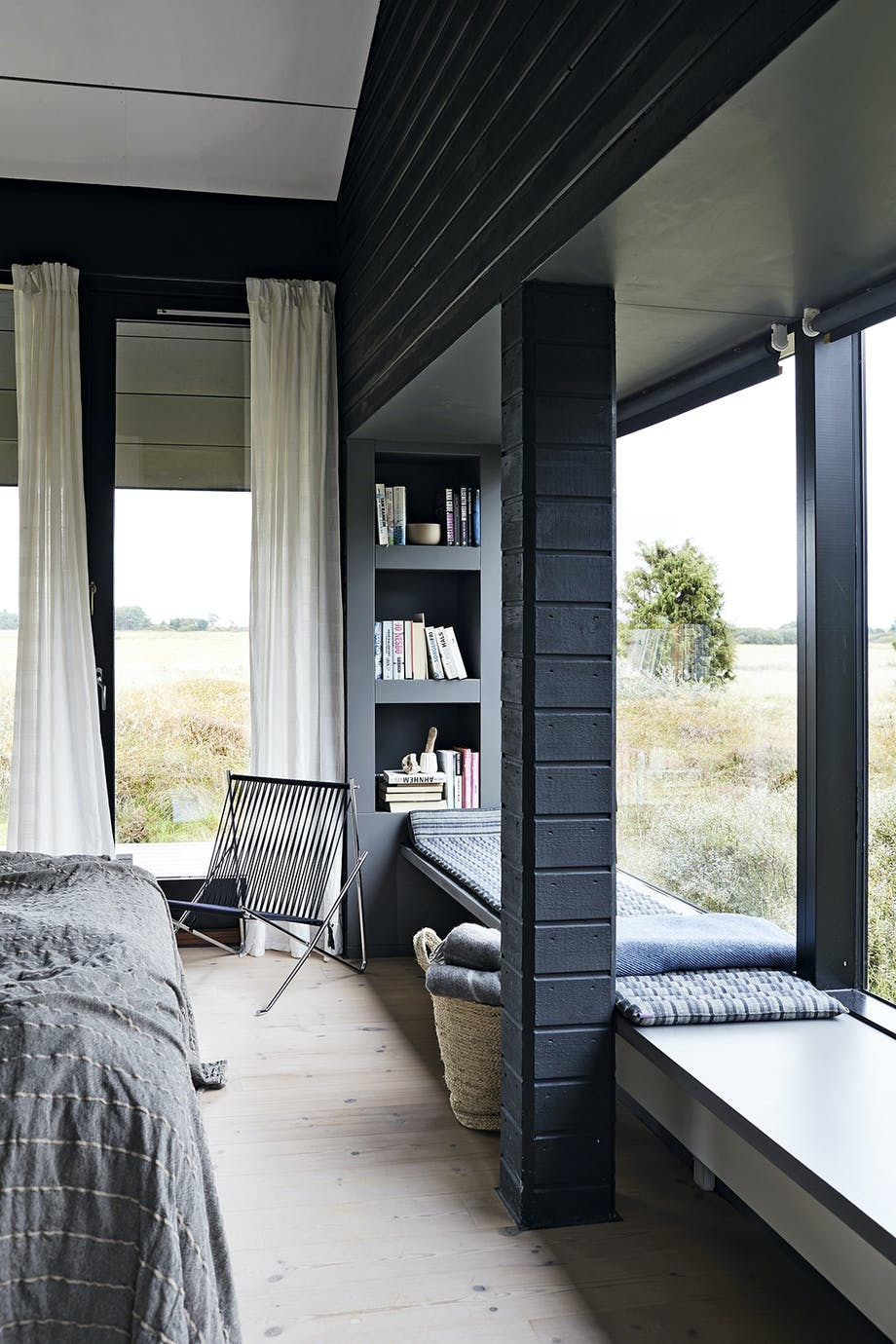 Soveværelse med stort vinduesparti med siddepladser og udsigt
