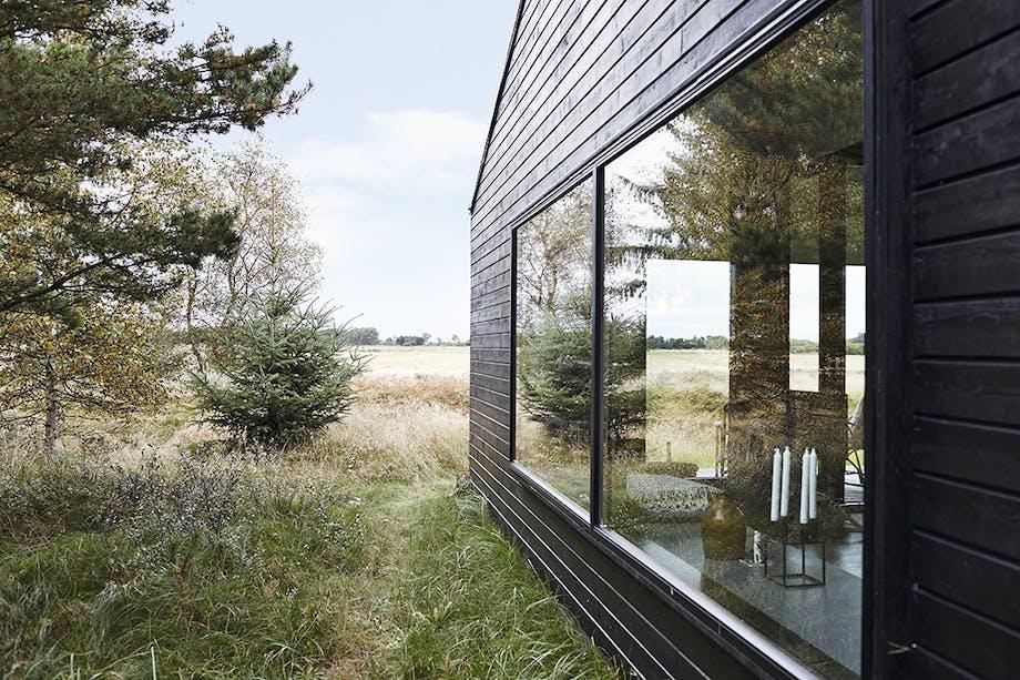 Sommerhus fra siden med kig ind i stuen og udsigt udover marken