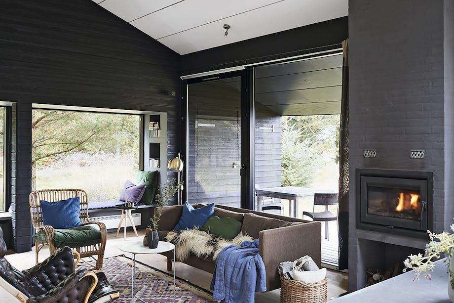 Opholdsstue med sofa, lænestol og brændeovn samt udgang til terrasse.