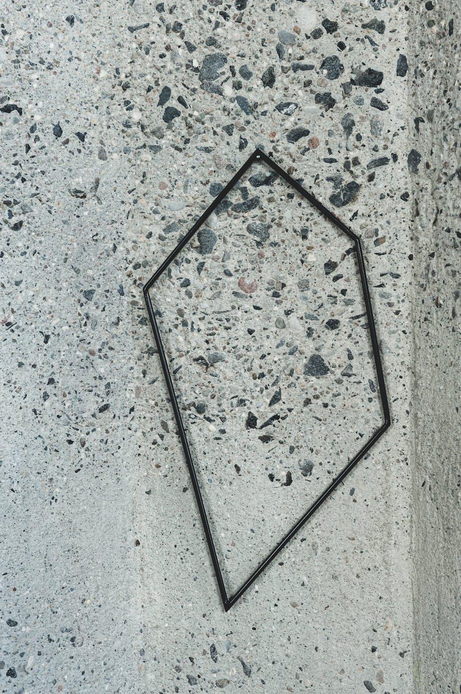 Betonvæg med et udsnit af en geometrisk ramme