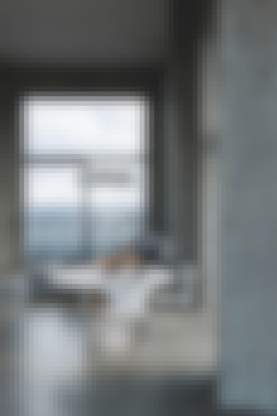Stue med havudsigt, betonvægge og et marmorbord