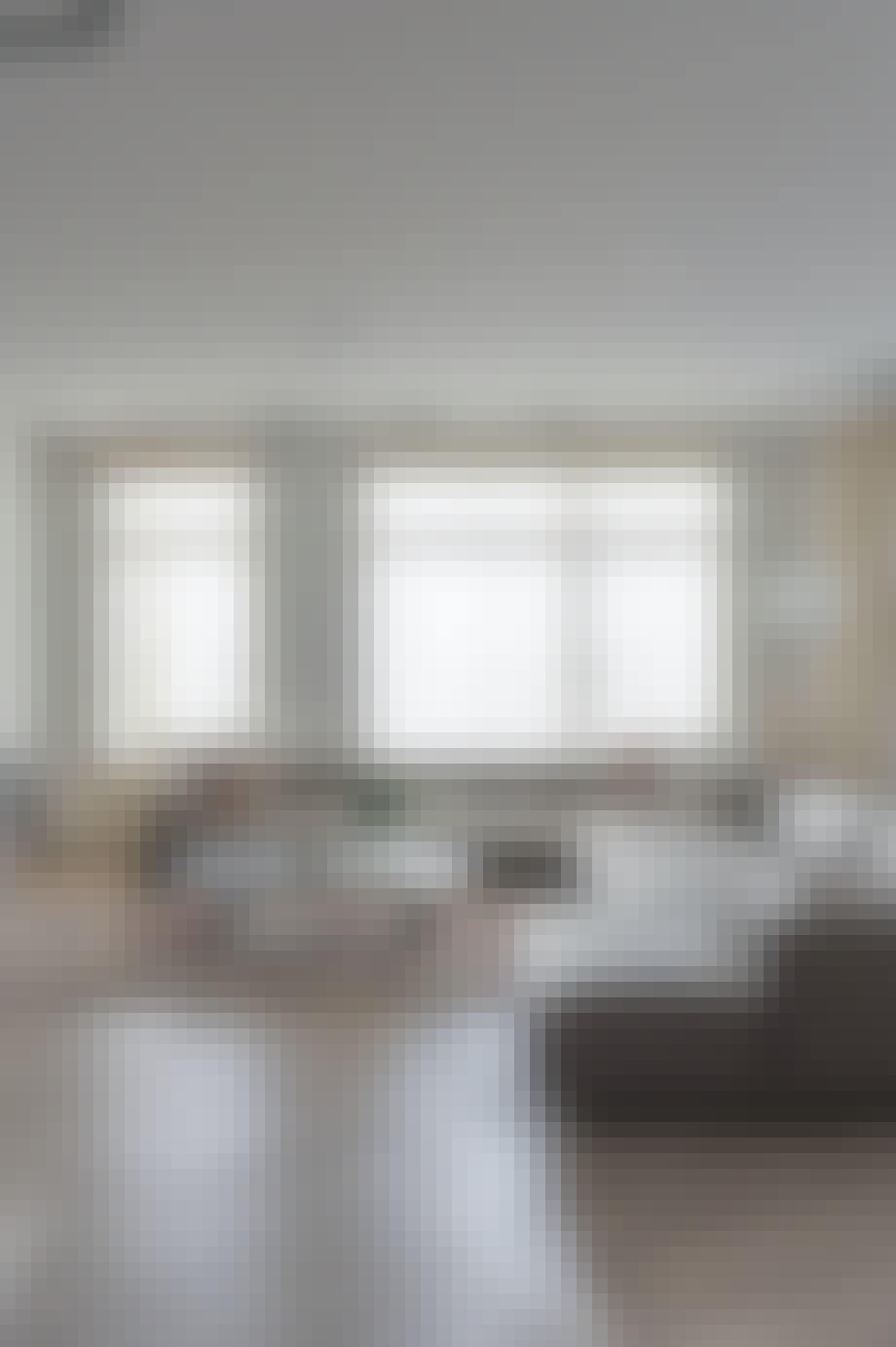 Stor sofa, marmorbord og luftige gardiner i stuen
