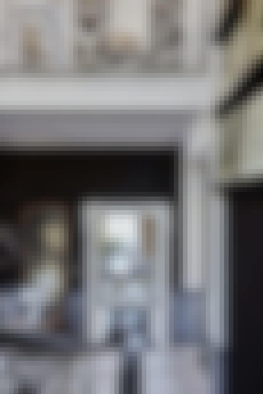 Hall med mørke farvetoner og marmorgulv