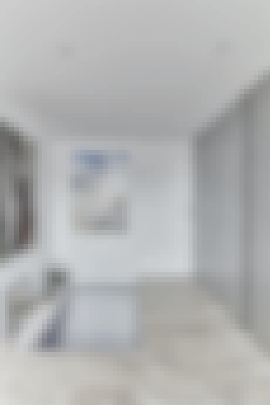 Entréen med gulv belagt med sølvtravertinsten og et flot maleri.