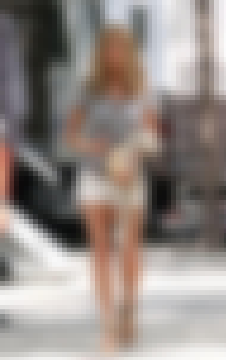 Jennifer Aniston i en sommerlig, kort shorts, sandaler og hatt.