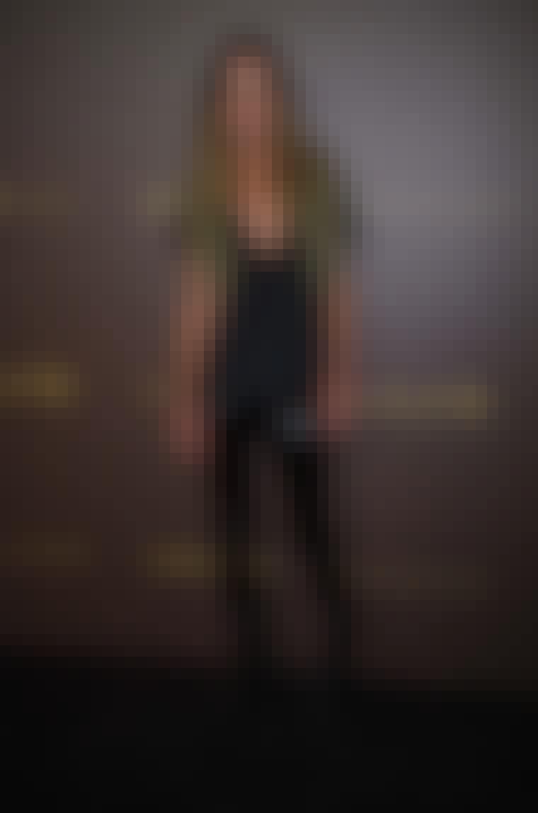 Toppmodell Erin Wasson ser rå ut i avslappet t-skjorte, skinnbukser og uniformsvest.