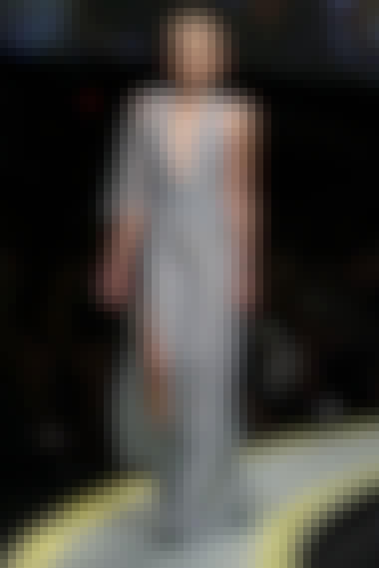 VERSACE: Dybe udskæringer, lange slidser, skinnende silke og skyer af tyl og fjer. Versaces stil er sexet og vovet. Designet er inspireret af kunstretninger fra antikken over barokken til renæssancen og futurismen, som kommer til udtryk i mønstre og fa...