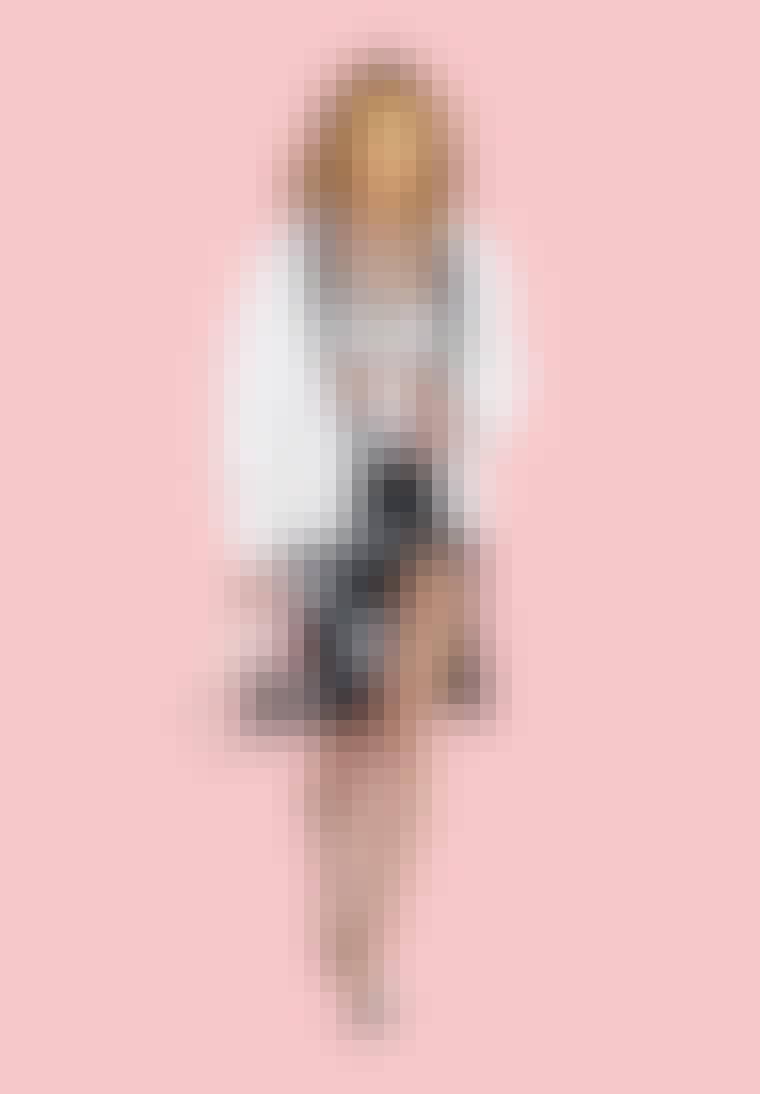 Samantha Jones iført hvis croptop, hvid blazer og sort nederdel fra chanel.