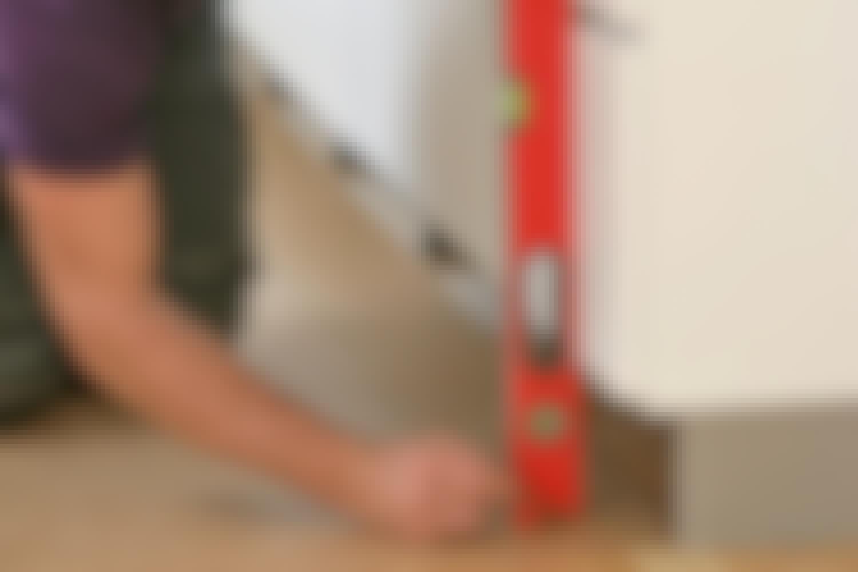 Sæt vaterpasset ned langs skabene, og tegn streger op, så gulvet ligger parallelt med skabene.