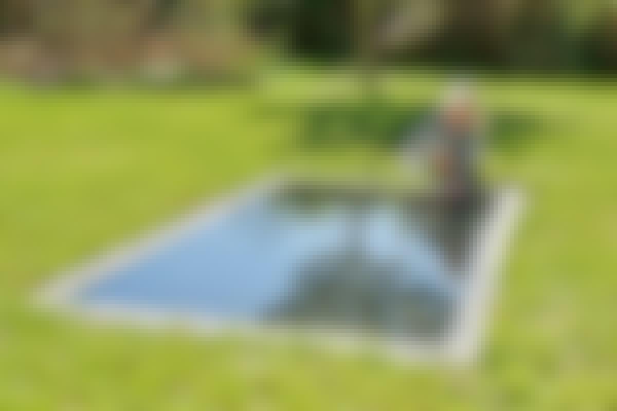 Veden peilimäisestä pinnasta heijastuu valoa, puutarhan kasveja ja taivaan värisävyjä.