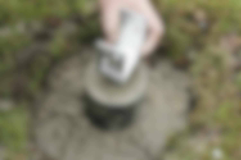 En stolpesko er av galvanisert jern. Den løfter stolpen, men holder den fortsatt fast til underlaget.