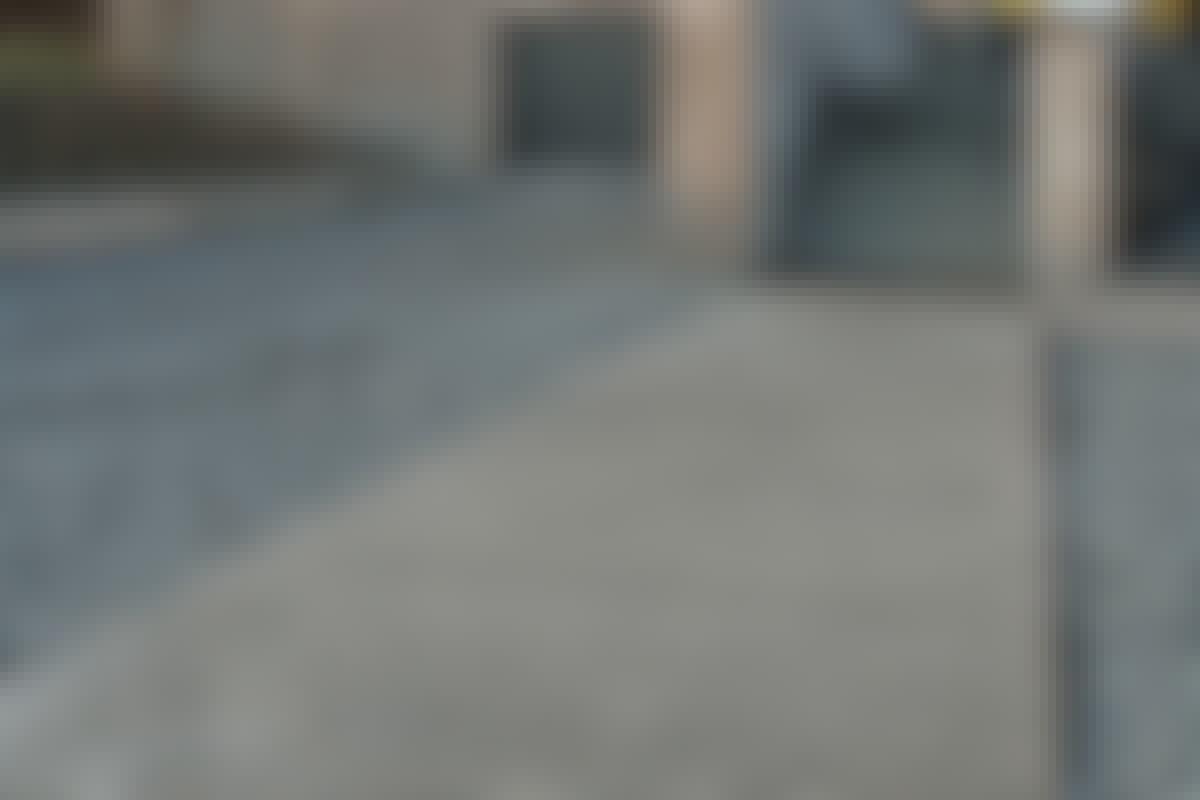 De fritlagte betonfliser med teaklister er en elegant løsning på en flisegang