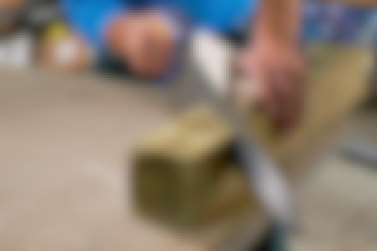 Kotitekoinen ohjuri pitää käsisahan suorassa kulmassa.