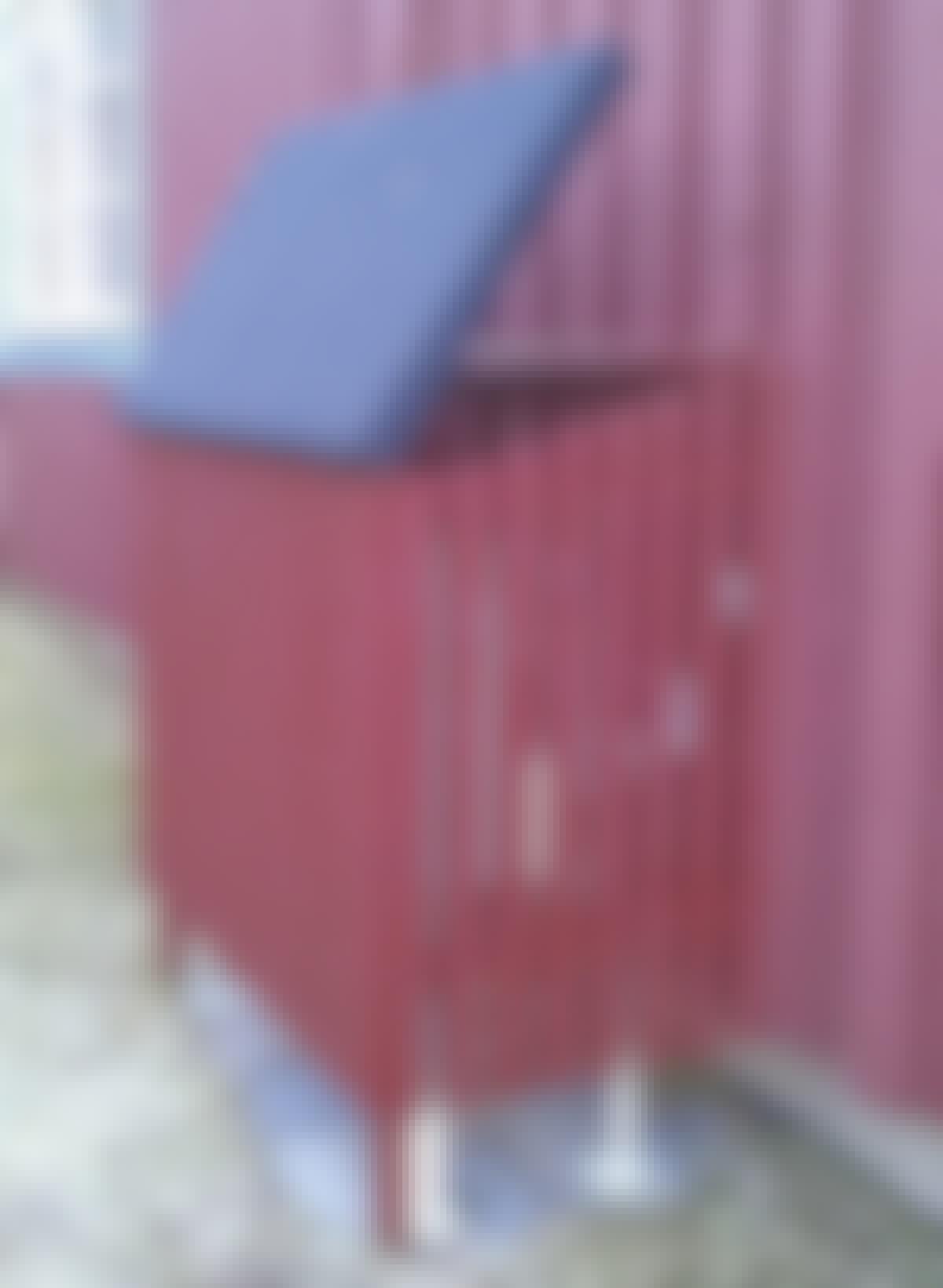 Varmepumpeskjuleren går i ett med den røde husveggen.