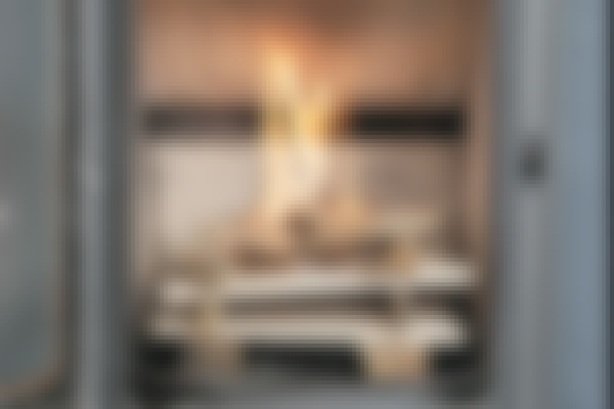 Flammene fra de små pinnene varmer opp kammeret før ilden kommer ned til større kubber. Det gir en ren forbrenning.