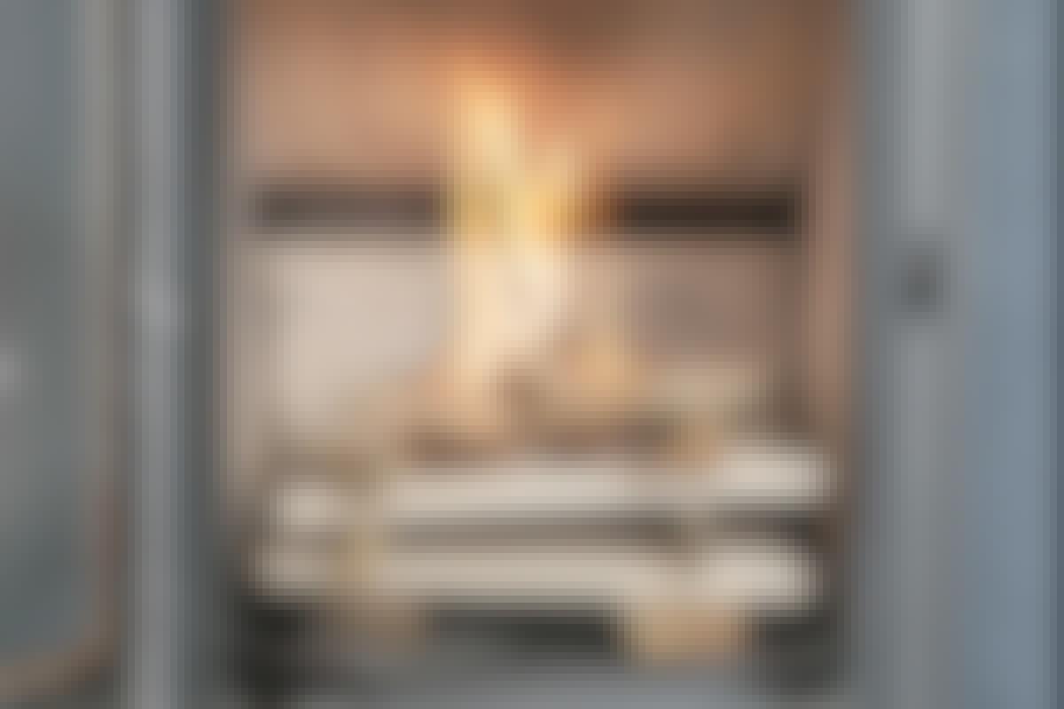 Flammerne fra de små pinde varmer kammeret op, inden ilden når ned til de større stykker. Det giver ren forbrænding.
