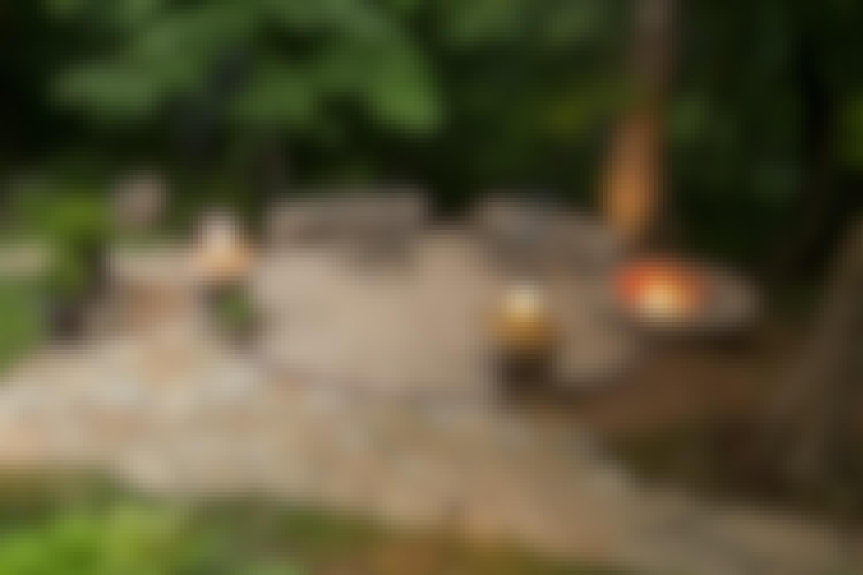 <strong>Hyggekrog i natursten </strong><br> Bålstedet er en del af terrassen i natursten i havens fjerneste krog. Her sidder du ikke rundt om bålet, som er placeret yderst på terrassen – i ly under skovens store træer.