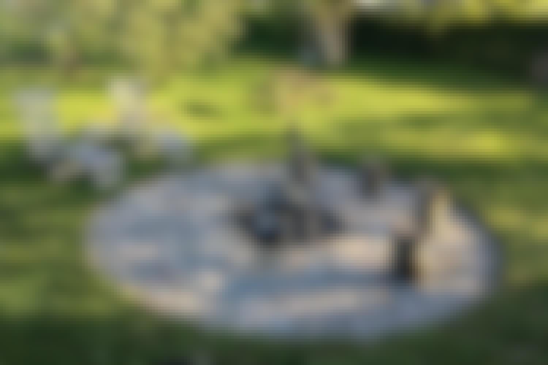 """<strong>Naturligt bålsted af pigsten</strong><br> Er du mere til det """"naturlige"""" look, kan du lave et bålsted af pigsten, som er lidt større sten med runde former. Stenene bankes på plads i grus, som lægges ud, når det øverste lag jord er fjernet."""