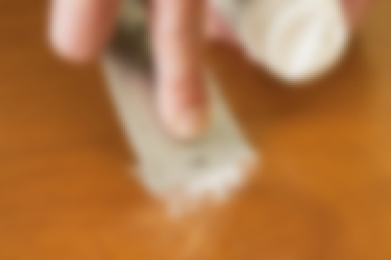 Den overskytende sparkelmassen trekkes av med en sparkel