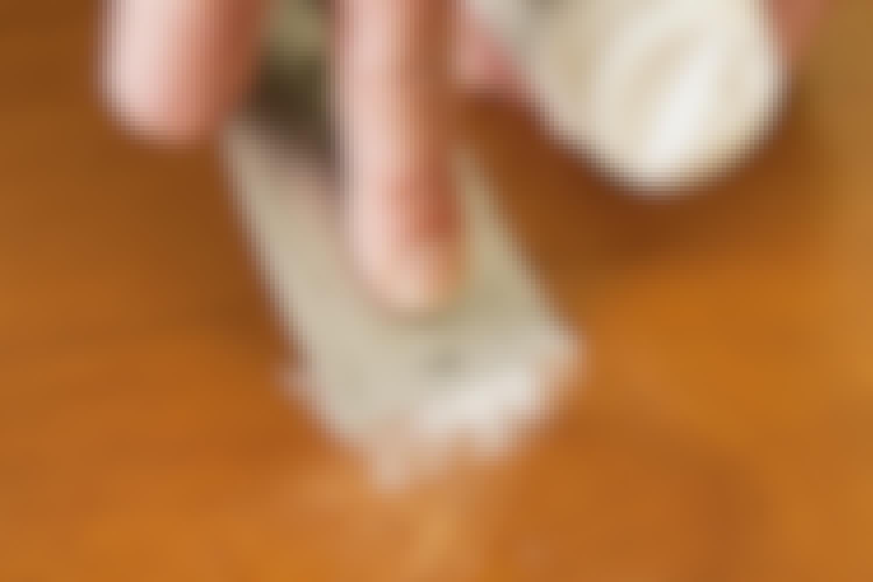 Överflödig spackelmassa dras av med en spackel