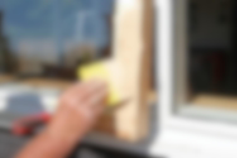 Reparationsmassan appliceras på fönstret i ett tjockt lager.