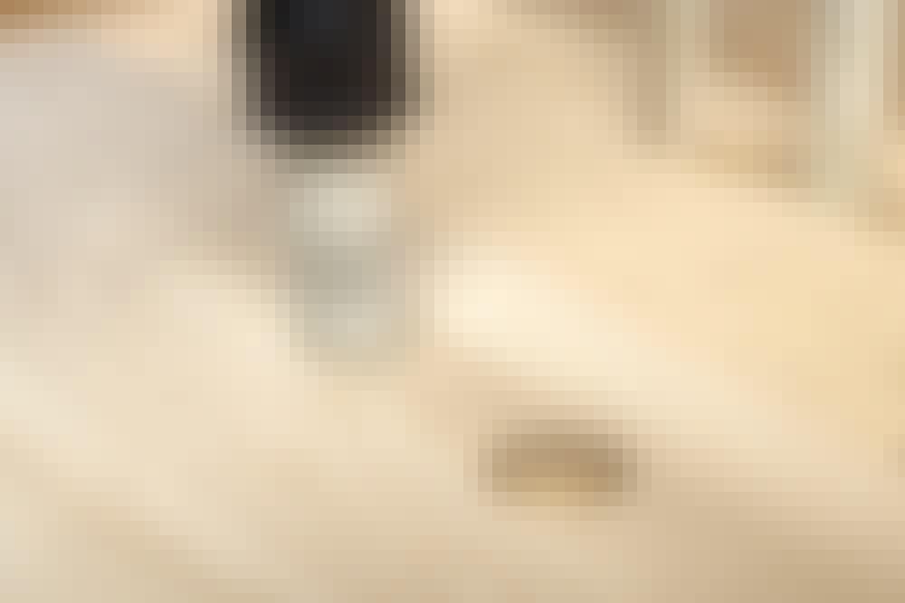 Rør midt mellom to langsgående gulvbord: Bordene legges med langside mot langside, og hullene bores med et koppbor – 10 mm større enn rørenes diameter, så det blir luft rundt rørene.