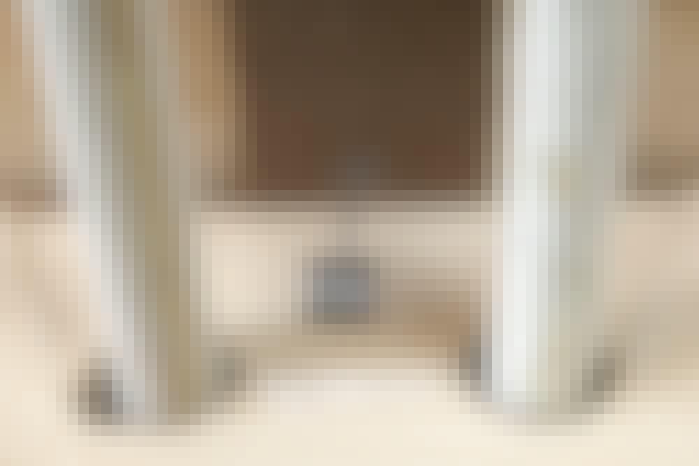 """Samling med """"kile"""" i gulvbræt: Mens limen tørrer, sættes kilen i spænd ved at trykke en afstandskile forsigtigt ned mellem kile og væg"""