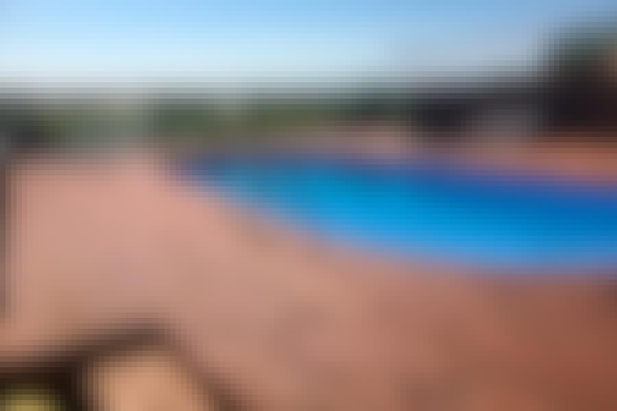 Fra poolen har man udkig gennem glasrækværket til marker og heste. Terrassen rundt om poolen er siden vokset i størrelse, så den nu er mellem 200 og 300 kvadratmeter.