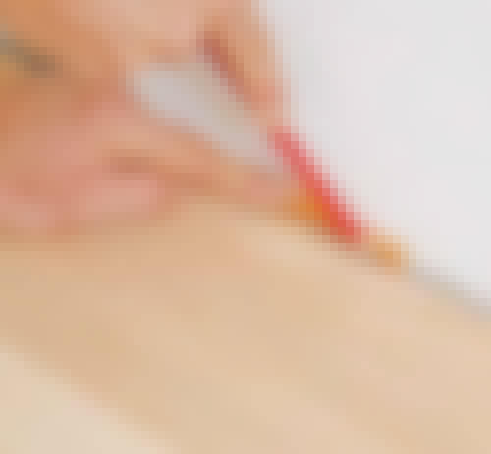 Gulvvarme trægulv: Når limen er tør - efter mindst en time - kan brædderne skubbes ind mod væggen.