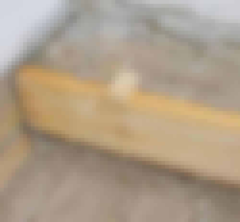 Golvvärme trägolv: Här har den första brädan fästs med en skruv och lim i båda ändar.