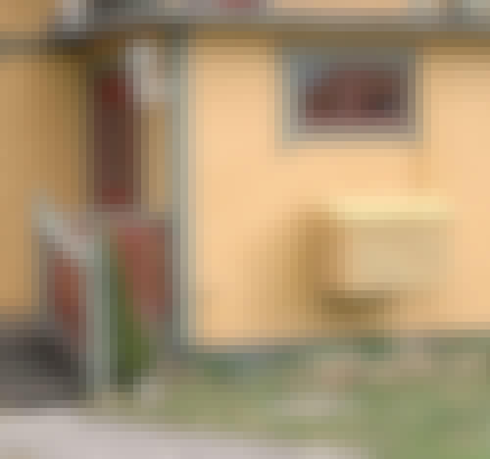 Värmepumpsskydd: Pumpen har byggts in i en liten låda med liggande lameller som har målats med samma färg som huset.