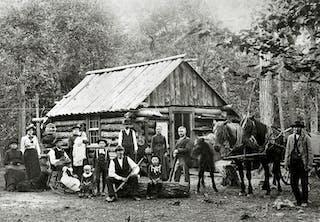 Svenska nybyggare i USA framför sitt boningshus i Minnesota.