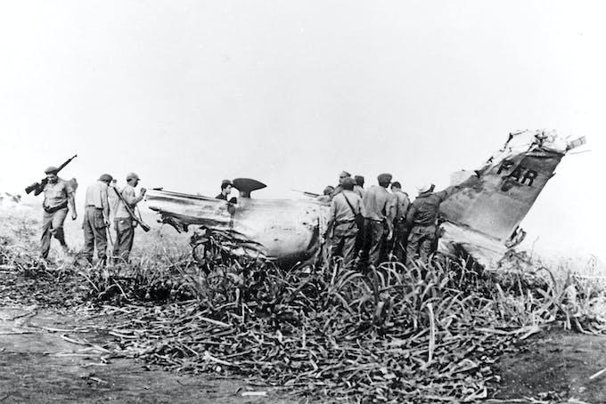Vraket efter en nedskjuten B-26 Invader undersöks av kubanska soldater. Planet sköts ner under invasionen av Grisbukten i april 1961.