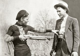 Bonnie poserar med ett gevär riktat mot Clyde.