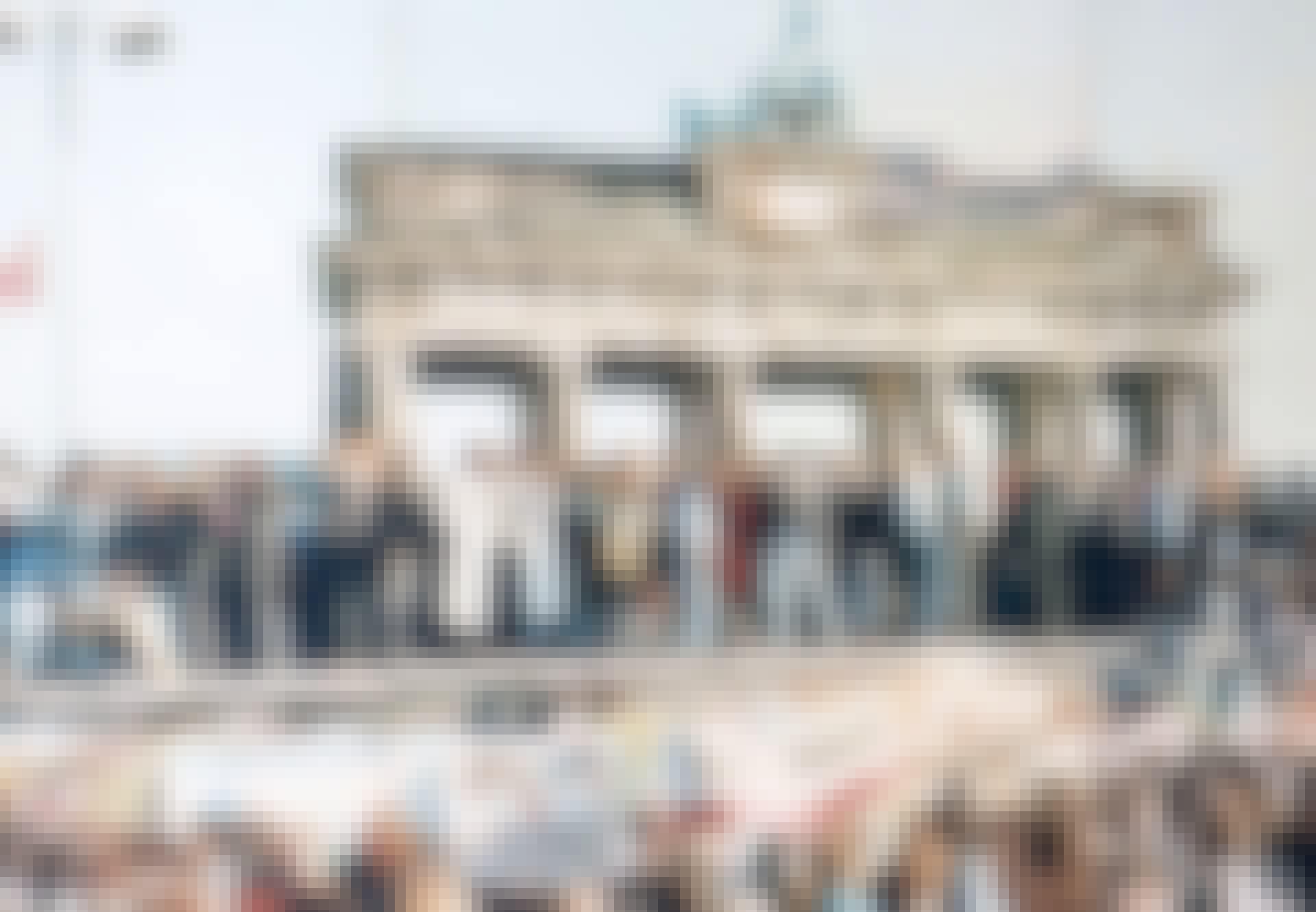 Människor står på Berlinmuren framför Brandenburger Tor