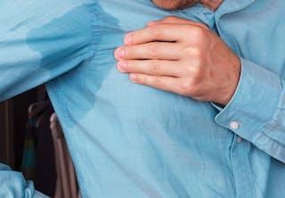 Mand har svedpletter under armene