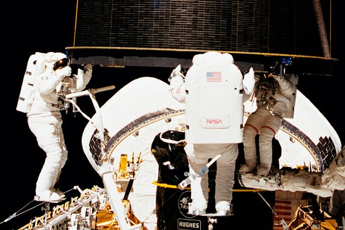 Tre astronauter griber en satellit i vægtløs tilstand, normalt vejer den 4 tons.