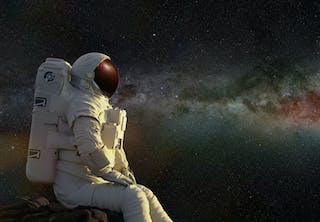 Astronaut tittar ut mot det universum vi aldrig kommer att kunna bo i.