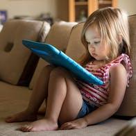 Skärmtid: Liten flicka ser på surfplatta