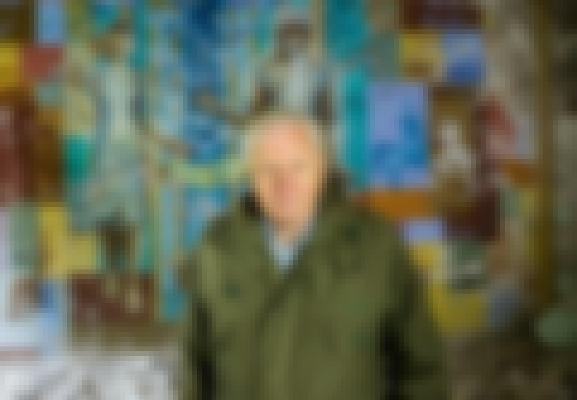 Sir David Attenborough foran en ødelagt murstensmur med grafitti
